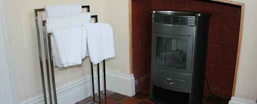 An image of a towel stand, standing infront of a black indoor stove with a small fire buring inside of it.