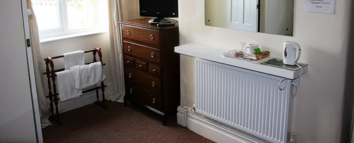An image of a bedroom with a window, radiator, chest of drawers, towel stand and mirror.
