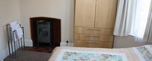 An image of a bedroom with a built in stove with a towel stand next to it, there is also a wardrobe.