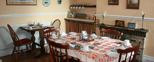An image of a traditional breakfast room with tables laid out with table cloths, cutlery and crockery.